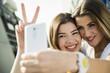 Zwei glückliche junge Frauen, die ein Selfie im Freien machen