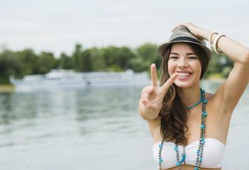 Lächelnde junge Frau zeigt Victory-Zeichen am Strand