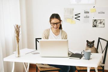 Frau und ihre Katze sitzten am Schreibtisch