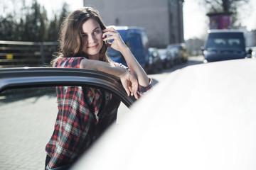 Junge Frau am Auto mit Handy