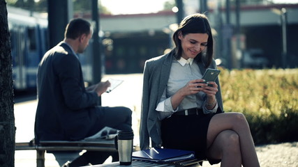 Young businesswoman texting, sending sms on smartphone on bench