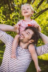 Vater mit Sohn auf seinen Schultern im Garten