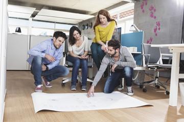 Vier Kolleginnen und Kollegen diskutierenein Konzept im Büro
