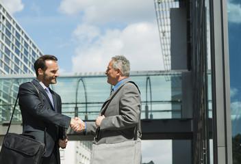 Zwei Geschäftsleute, die draußen Hände schütteln