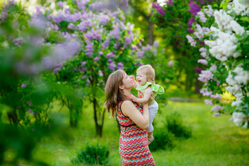 happy mother with baby garden of blooming lilacs.