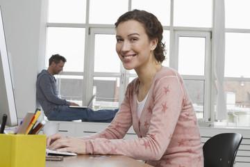 Lächelnde Frau am Schreibtisch mit Mann im Hintergrund