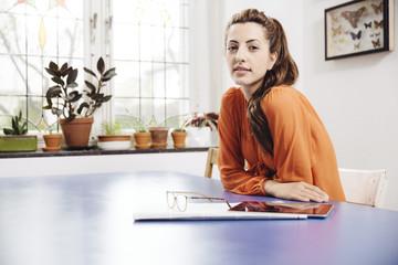 Junge Frau mit Tablet-Computer und Zeitung