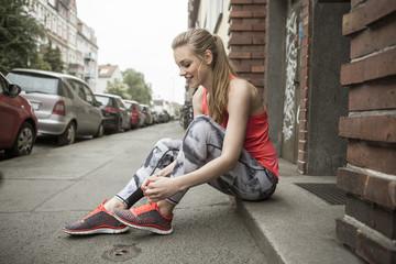 Deutschland, Niedersachsen, Hannover, junge Joggerin sitzt auf Bürgersteig, bindet ihre Schuhe