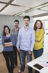 Gruppenbild der vier Kollegen stehen im Büro
