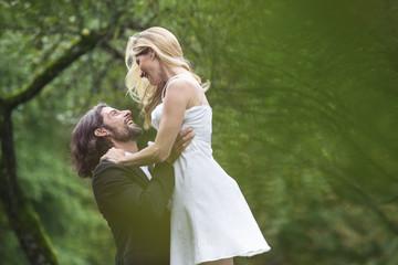 Glücklicher Bräutigam hebt Braut im Garten