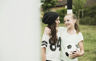 Glückliche Teenager-Mädchen auf einem Fußballplatz