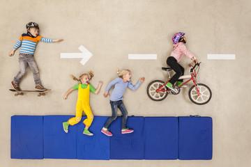 Kinder beim Radfahren, Skateboardfahren und Laufen auf der Straße