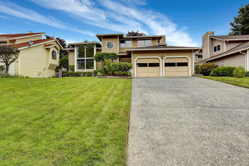 House exterior with large window. Garage and spacious driveway