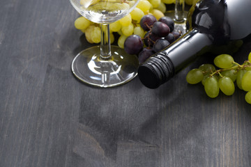 bottle of red wine, empty glass and grapes on dark wooden table