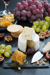Camembert with fresh honey, grapes and nuts, vertical