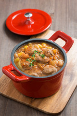 delicious vegetable stew with sausages in a pan on wooden board