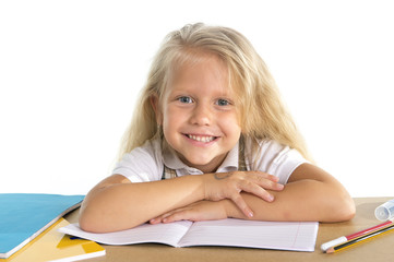 cute little schoolgirl smiling happy on desk doing homework