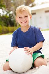 Young Boy Playing Game Of Volleyball In Garden