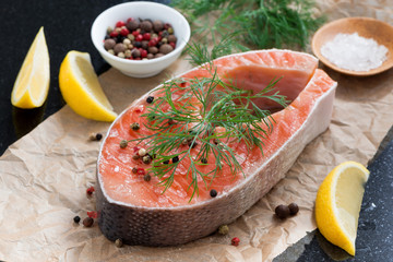 raw salmon steak, lemon and spices prepared for cooking