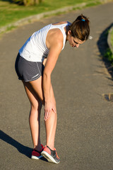 Female athlete suffering a calf muscle cramp injury while runnin