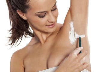 young beautiful woman shaving her armpits