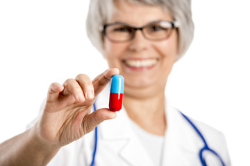 Female doctor holding  a pill