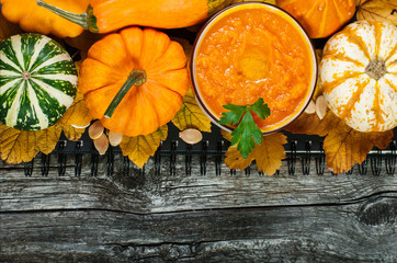 Pumpkin cream-soup and pumpkins on the wooden background