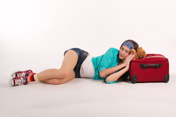 young woman lying on the floor with suitcase