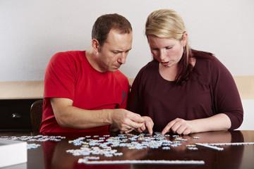 Puzzle, Ehepaar setzt Puzzleteile zusammen