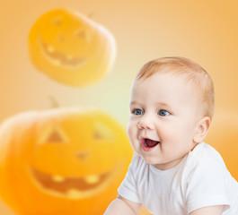 smiling baby over pumpkins background