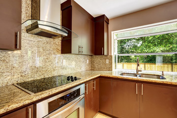 Modern kitchen room with matte brown cabinets and granite trim.