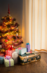 Christmas tree with gifts and old suitcase