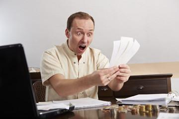 Mann bei der Buchführung, schockiert
