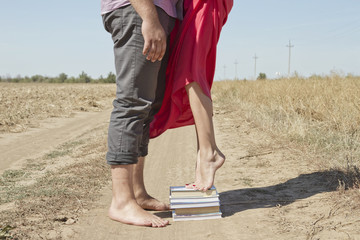 A girl stands on a stack of books to reach out and kiss the guy