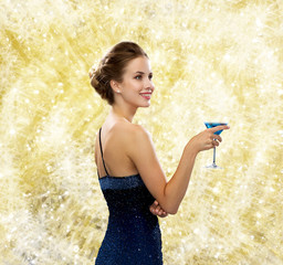 smiling woman in evening dress holding cocktail