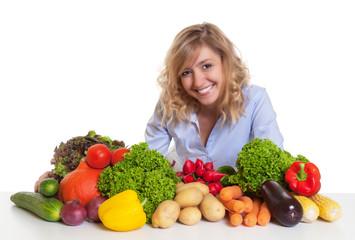 Frau mit blonden Locken und Gemüse schaut zur Kamera