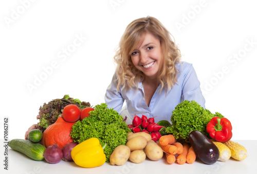 canvas print picture Frau mit blonden Locken und Gemüse schaut zur Kamera