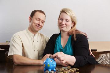 Sparen, Ehepaar wirft Zwei Euro in den Sparschwein 2