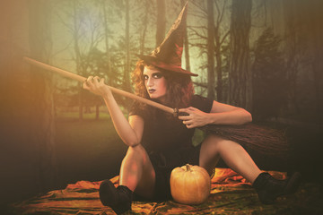 Young woman dressed like a witch. She is with broom and pumpkin