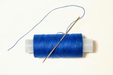 катушка синих ниток с иголкой