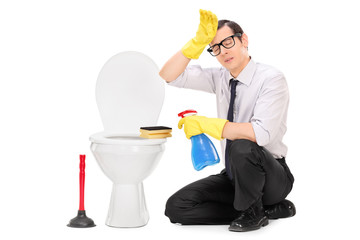 Exhausted young man cleaning a toilet
