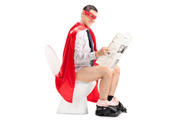 Superhero reading the news seated on a toilet