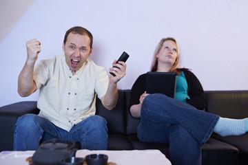 Fernsehen, Mann jubeln, Frau gelangweilt