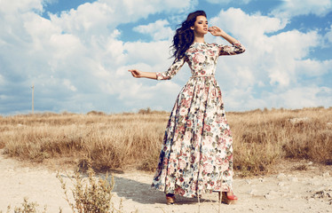 woman in luxurious floral dress posing in summer field