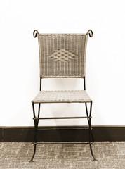 rattan chair against a white wall