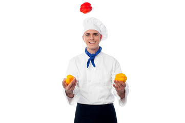 Skilled chef juggling with capsicums