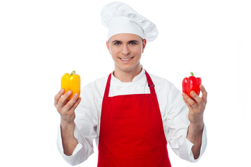 Chef in uniform showing capsicums