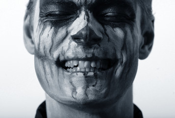 portrait of a man in make-up Halloween. drawing a vampire on his