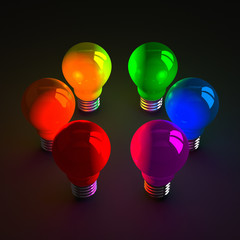 Colored glowing light bulbs standing on dark