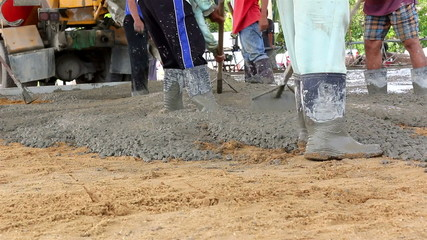 Construction workers spreading freshly poured concrete mix